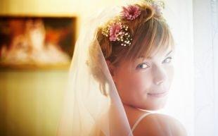 Свадебные прически с фатой, романтичная свадебная прическа на короткие волосы с челкой и цветами в волосах